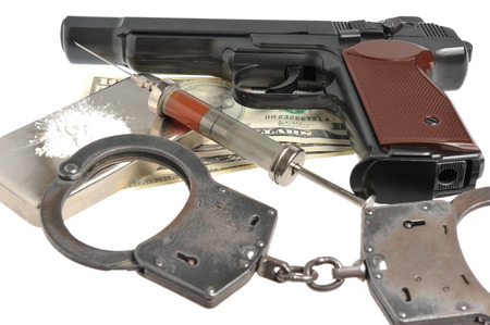 Drugs, syringe with blood, pistol, handcuffs and money isolated photo