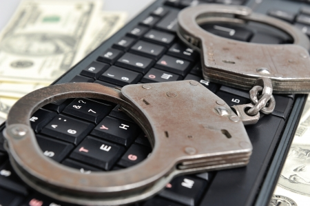 Handcuffs on the keyboard against money photo