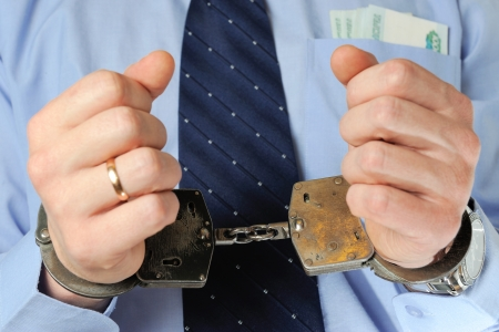 crook: Man holds his hands in handcuffs before itself with money in the pocket Stock Photo