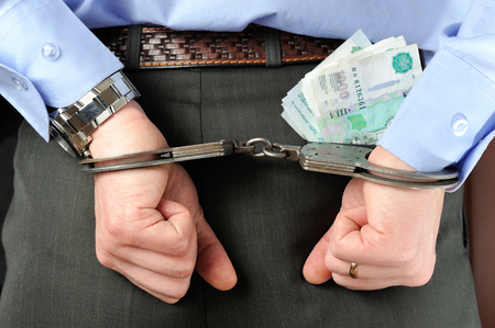 Man hands in handcuffs with money in his pocket photo
