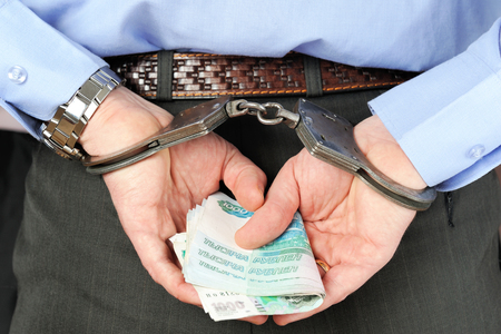 Man in handcuffs holds banknotes in his palms behind his back photo