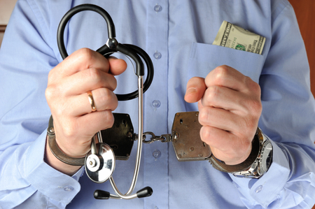 paid medicine: Man holds his hands with stethoscope in handcuffs before itself with money in the pocket
