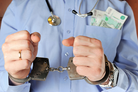 Man with stethoscope holds his hands in handcuffs before itself with money in the pocket photo