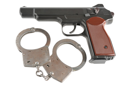 Pistol with handcuffs isolated on white  Stock Photo - 25406691