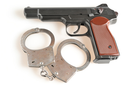 Pistol with handcuffs isolated on white Stock Photo - 25406694