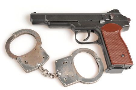 Pistol with handcuffs isolated on white  Stock Photo - 25406701