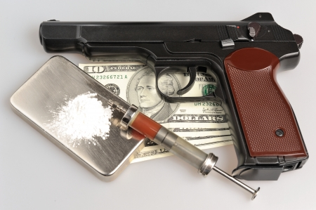 Drugs, syringe with blood, pistol, money on gray background photo