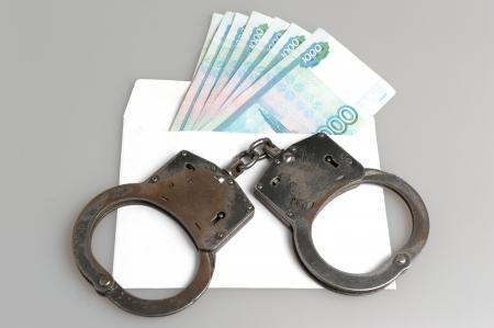 fraudster: Manette e busta bianca con il denaro su sfondo grigio