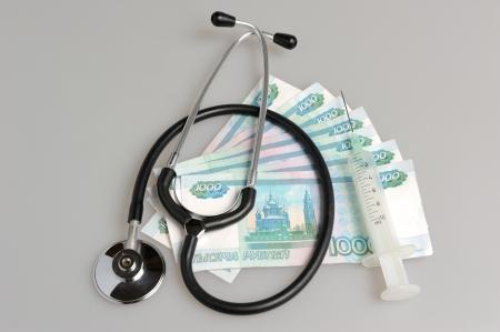 fraudster: Stetoscopio, siringa e denaro su sfondo grigio