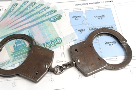 fraudulent: Handcuffs, money with the plan of the house on a white background