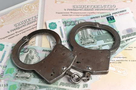 Handcuffs and money on the ownership certificates photo
