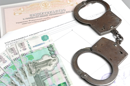 Handcuffs, money against the certificate of registration of property rights and cadastral extract photo