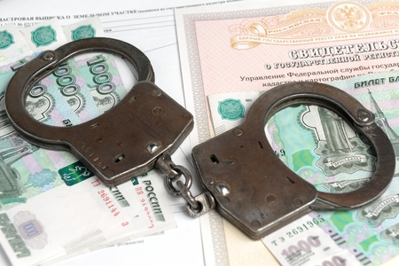 faker: Handcuffs, money against the certificate of registration of property rights and cadastral extract closeup Stock Photo