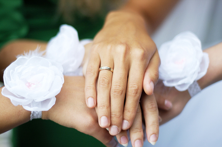 betroth: Hands of young bridesmaids with white flowers on the wrists and hand of bride with golden ring on the finger