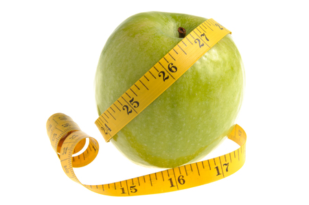 dietology: One green apple with measuring tape isolated on white  Stock Photo