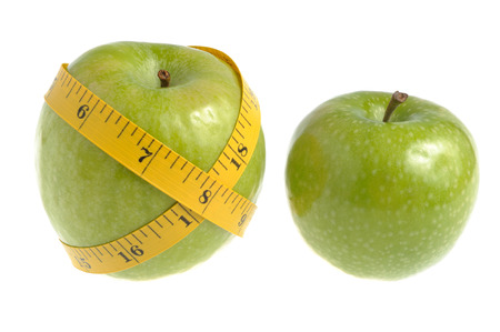 dietology: One green apple wrapped with measuring tape and another green apple isolated on white