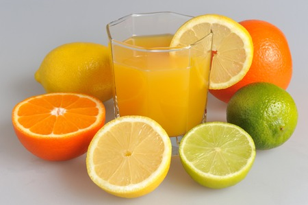 dietology: Some kind of citrus with the glass filled with citrus juice on the gray Stock Photo