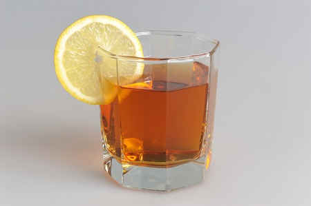 dietology: Glass with a slice of lemon filled with lemon tea on grey