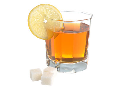 dietology: Glass with a slice of lemon filled with lemon tea and refined sugar isolated on white