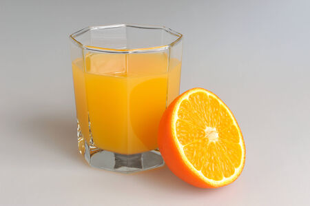 dietology: A half of orange with a glass filled with citrus juice on gray  Stock Photo
