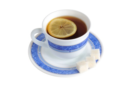 A cup of tea with one slice of lemon within and refined sugar on saucer isolated on white background photo