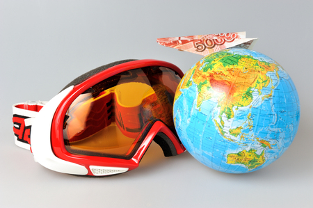 Mountain ski mask, globe and airplane of money on it on gray background photo