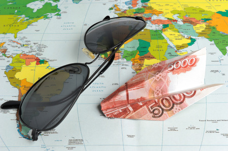 Sunglasses and origami plane made from money on the world map