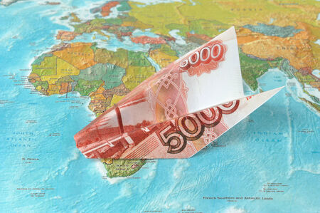 Origami plane made from rubles on the map photo