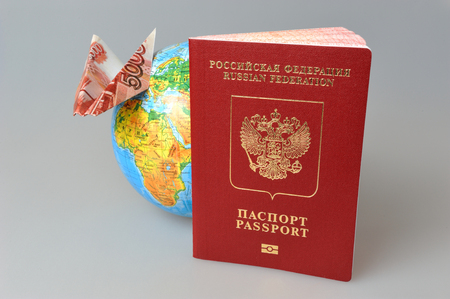 Russian International passport, globe and origami plane made from money on gray background photo