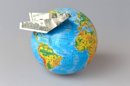 Globe with origami plane made from dollar on gray background photo