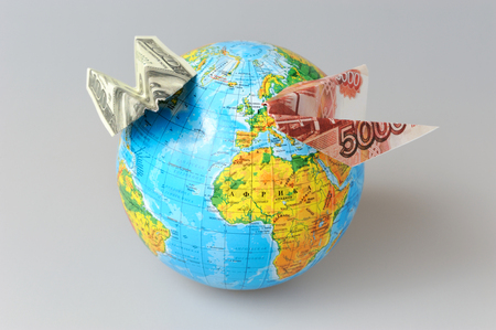 Globe with origami planes made from money on gray background photo