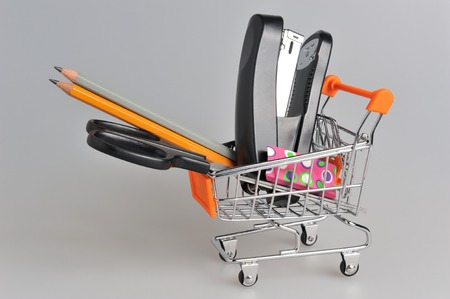 Shopping cart and stationery within on gray background photo