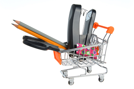 Shopping cart and stationery within isolated on white background photo