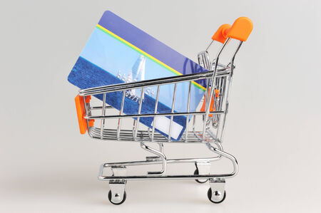 non cash: Shopping cart and credit card within on gray background