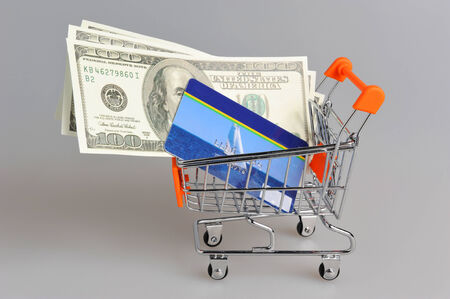 non cash: Credit card and money within shopping cart on gray background