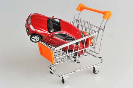 Toy car in shopping cart on gray background photo