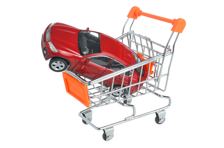 car retailer: Toy car in shopping cart isolated on white background Stock Photo
