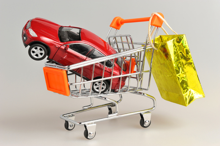 Toy car in shopping cart with hanging gold package on gray background photo