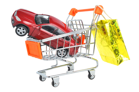Toy car in shopping cart with hanging gold package isolated on white background photo
