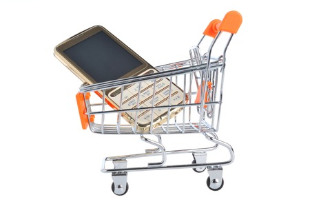 Cell phone in supermarket pushcart isolated on white photo