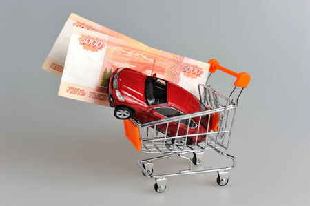 Toy car with money in shopping cart on gray background photo