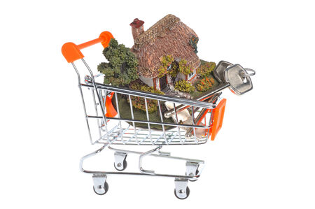 Model of house with keys in the shopping cart isolated on white background photo