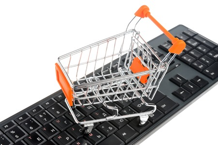 acquirer: Shopping cart on black keyboard isolated on white background