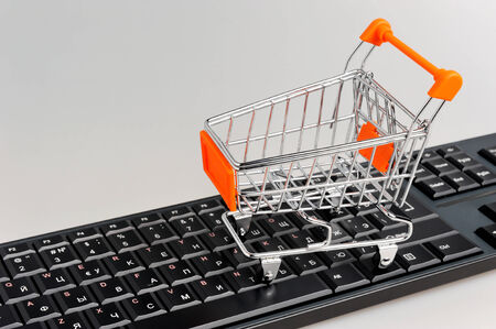 Shopping cart on black keyboard on gray background photo