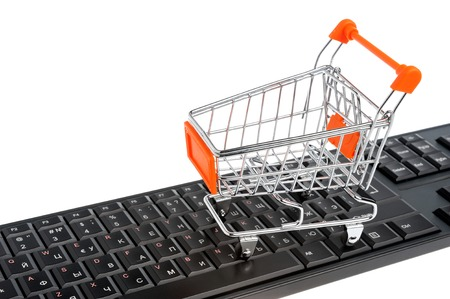 Shopping cart on black keyboard isolated on white background photo