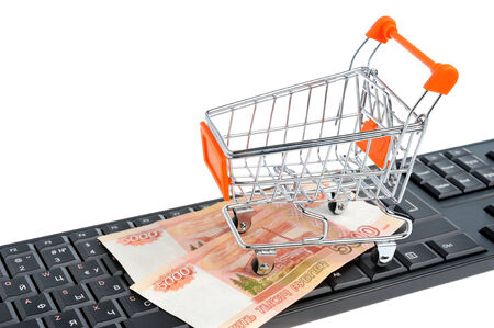 acquirer: Shopping cart with money on black keyboard isolated on white background Stock Photo