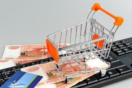 Shopping cart with money and credit card on black keyboard on gray background photo