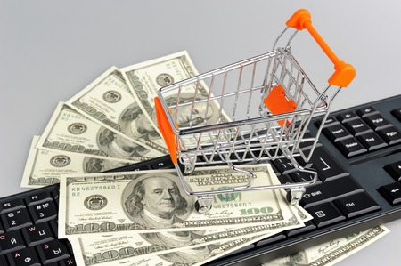 acquirer: Shopping cart with money on black keyboard on gray background