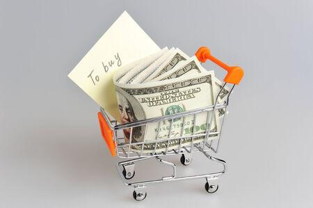 carretilla de mano: D�lares con la lista de la compra en la carretilla de mano sobre fondo gris