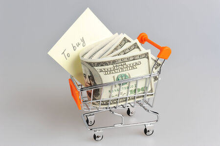 pushcart: Dollars with shopping list in pushcart on gray background
